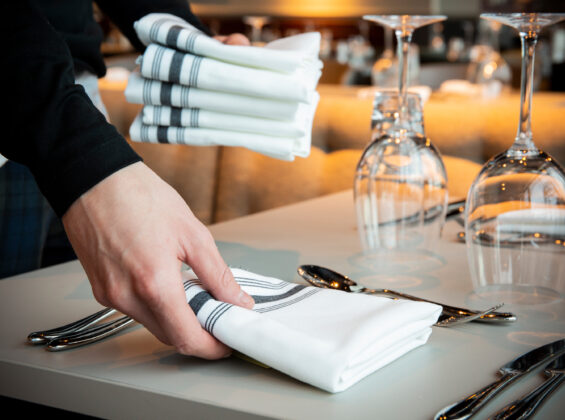 Black Stripe Bistro Style Napkin s being placed on a table