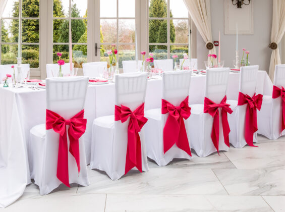 Arctic White table cloths and stretch chair cover with Pink Fuchsia napkins and chair sashes