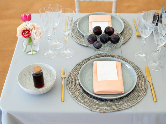 Two Coral napkins on a Pebble Grey table cloth